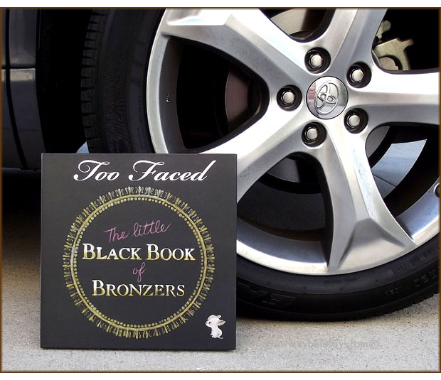 Too-Faced-The-Little-Black-Book-of-Bronzers-next-to-car-tire